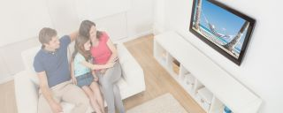 Family watching thin television mounted on wall