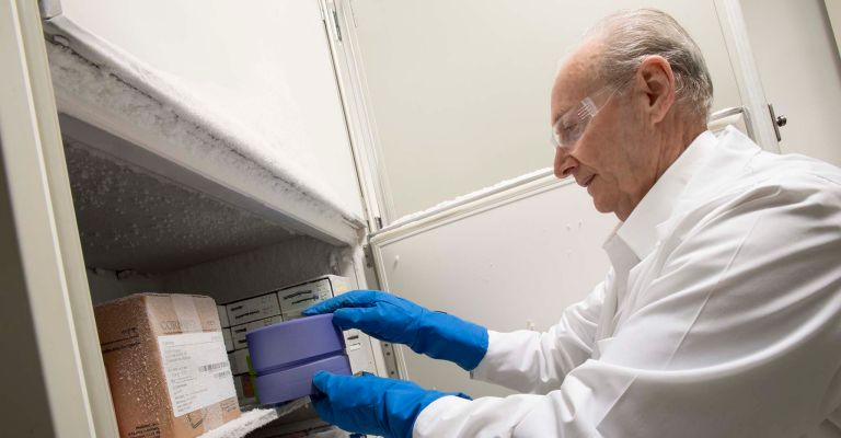 Scientist handling a CoolBox in a freezer