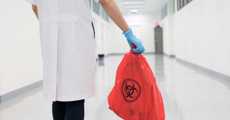 Scientist holding bag of waste from lab