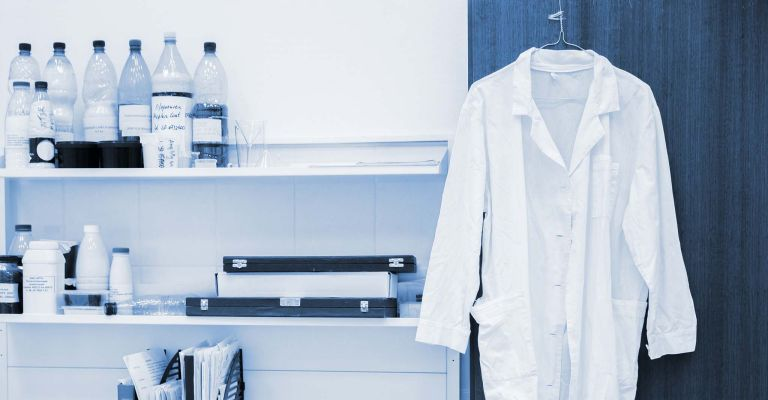 White lab coat hanging in lab