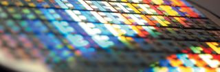 "Extreme closeup of tiny, colorful glass ""tiles"" of semiconductor"