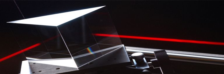 Bright red laser beam travels through optic component