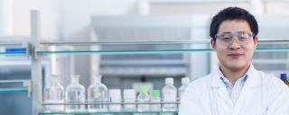 Man in lab coat fronts row of glass beakers