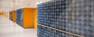Hallway walls covered in decorative blue, white, orange glass finishes