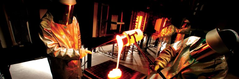 Workers in protective suits pour molten glass from crucible