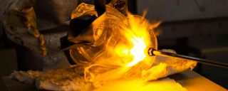 Closeup of metal, glass being forged in fire