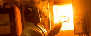 Technician in protective suit holds crucible of molten glass