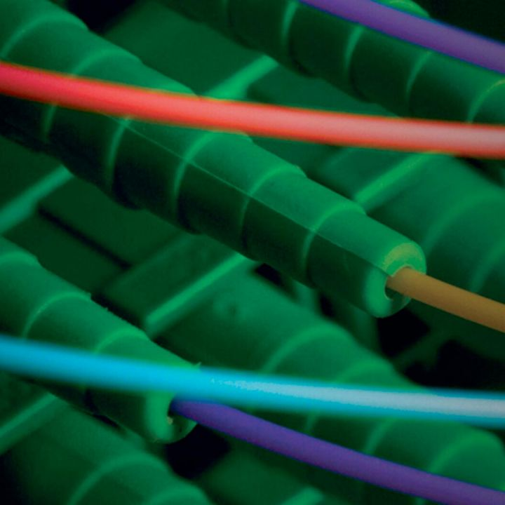 Extreme closeup of multicolored fibers attached to green housings