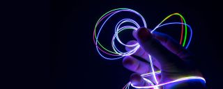 Hand holds loops of lighted fibers, glowing in dark