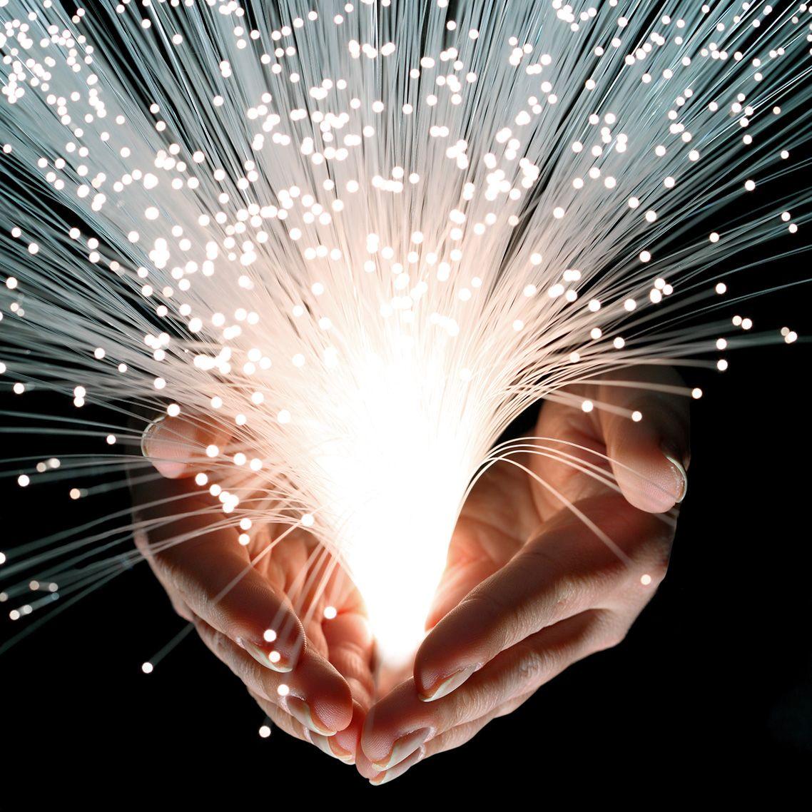 Hands cradle bright white burst of lighted stands of fiber