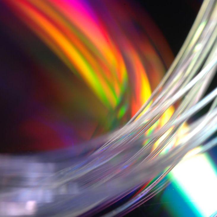 Bundle of clear glass fibers up close, multicolored backdrop
