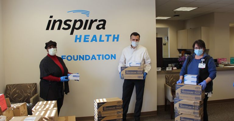 People holding boxes of surgical masks