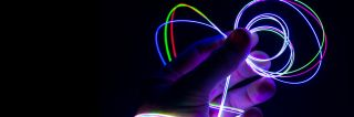 Hand holds bright, colorful loops of Fibrance in dark